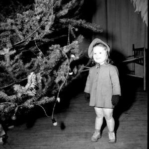 A little girl by a Christmas tree at Hanford