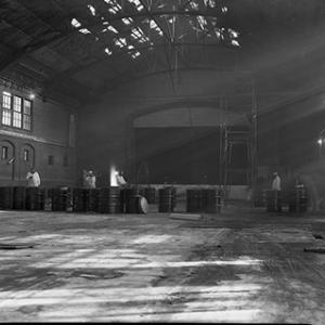 Unit IV interior; workers with several 55 gal. drums on otherwise empty floor. Photo courtesy the Mound Museum.