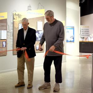 Clay Perkins and Jim Sanborn cutting the ribbon to open the exhibition