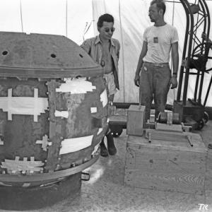 """Louis Slotin and Herb Lehr at the assembly of the Trinity """"Gadget.""""  The uranium tamper is on the box in front of Lehr."""
